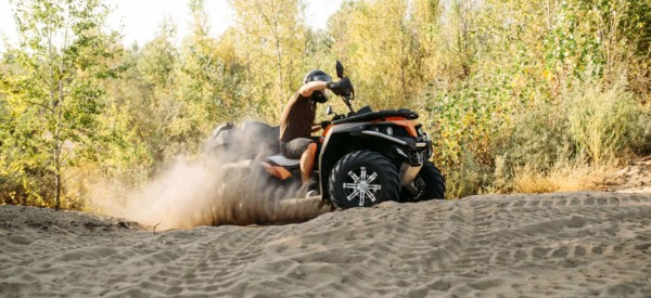 Atv freeriding in sand quarry, extreme sport. Male driver in helmet riding on quad bike in sandpit