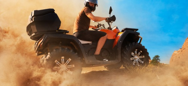 Atv in dust clouds, sand quarry on background. Male driver in helmet on quad bike in sandpit