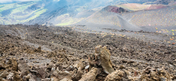 travel to Italy - cloud on frozen lava field on Mount Etna in Sicily in summer day