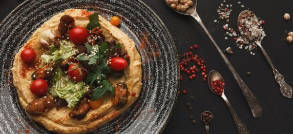 Chickpea hummus with mussels and vegetables in stylish bowl. Healthy traditional vegetarian beans pasta with olive oil and fresh pita bread served on black table background