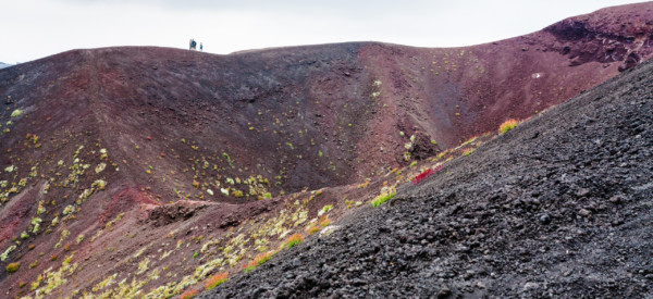 travel to Italy - people on edge of crater on Mount Etna in Sicily in summer day