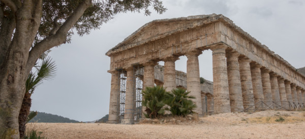 The ruin of the old Roman temple with an olive tree on a cloudy day in Segesta, Sicily, Italy.