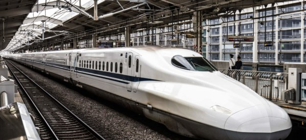 A Shinkansen high-speed bullet train pulling into a train station in Japan