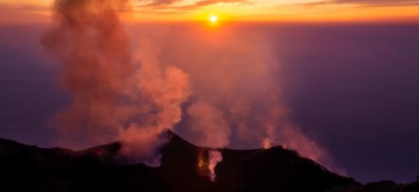 Smoking erupting volcano on Stromboli island at colorful sunset, Sicily, Italy