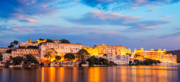 Rajasthan indian tourist landmark - Udaipur City Palace complex in the evening twilight with dramatic sky - panoramic view. Udaipur, India