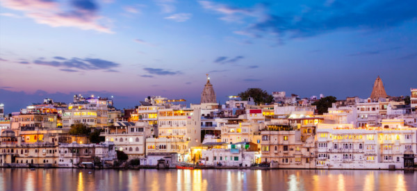 Evening view of illuminated houses on lake Pichola in twilight, Udaipur, Rajasthan, India