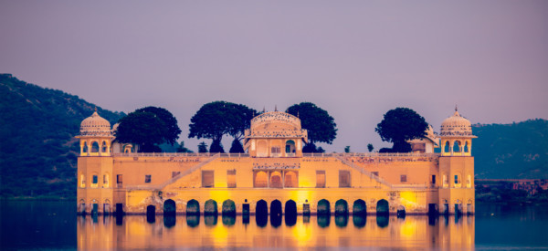 Vintage retro hipster style travel image of Rajasthan landmark - Jal Mahal (Water Palace) on Man Sagar Lake in the evening in twilight.  Jaipur, Rajasthan, India